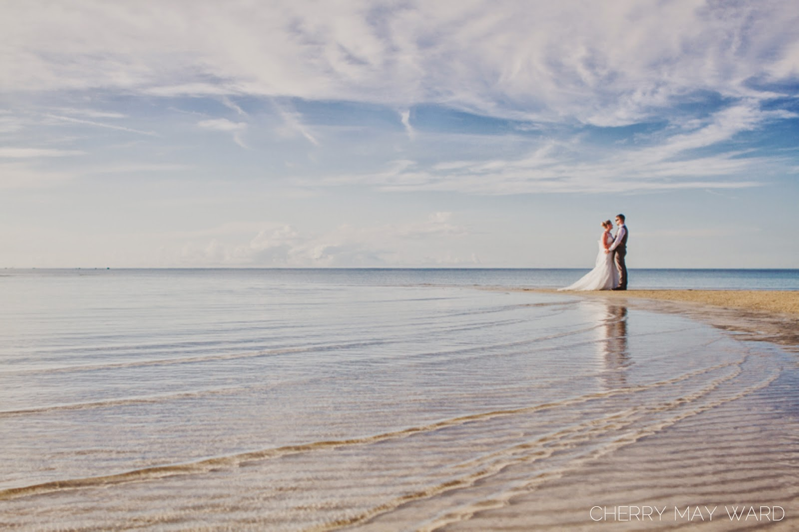 bride and groom standing on a sand bar with water in between them, beautiful clear water with sand ripples from the waves, Koh Samui trash the dress session, Samui wedding