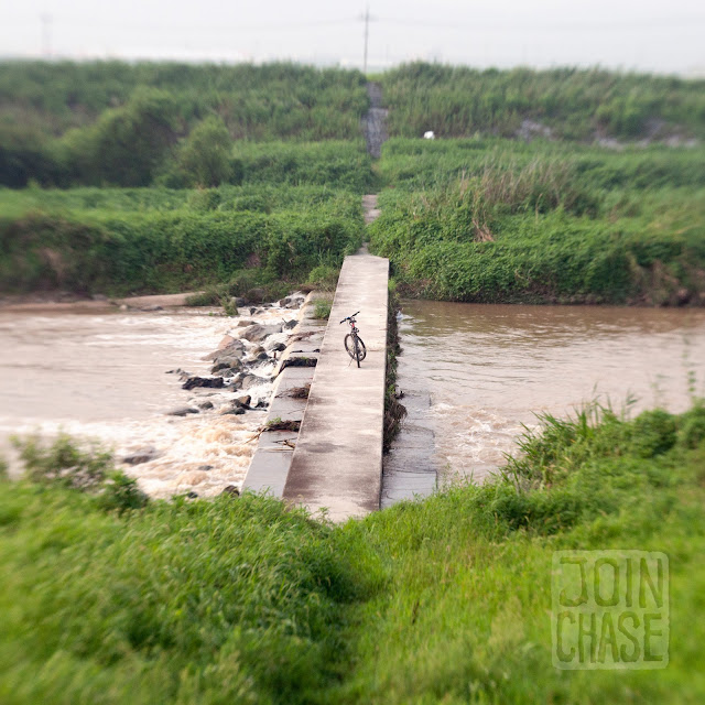 A bike on a small bridge over a river in rural, South Korea.
