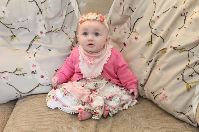 baby wearing floral dress from next with pink cardigan and floral headband