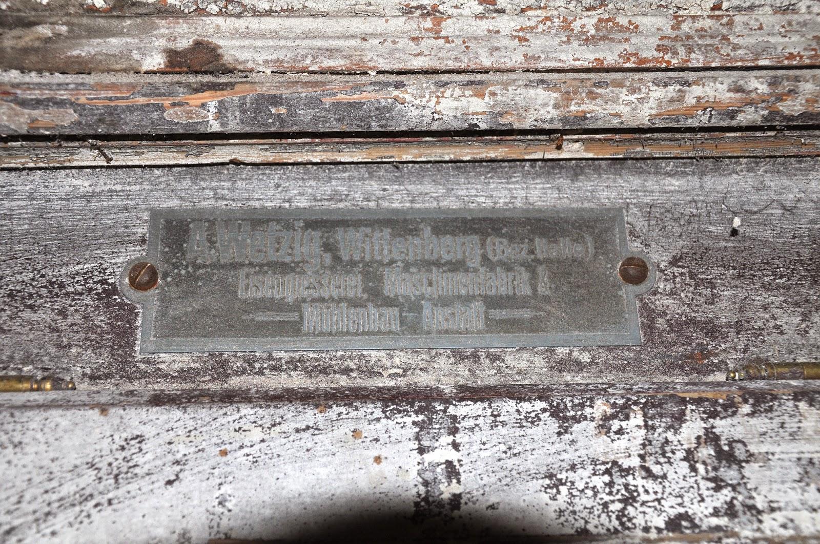 """Wnętrze młyna - parter. Od strony północnej znajdowała się dwie """"maszyny"""" do przemiału - tu ze zbliżeniem tabliczek. Czerwiec 2014, foto. KW."""