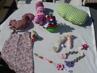 tafel met kussen in eekhoorn- en appel vorm, knuffel in vorm van een rups, diverse rattels (zeepaardje, aapje en muis), stapelspeeltje, jurkje en gehaakte speen