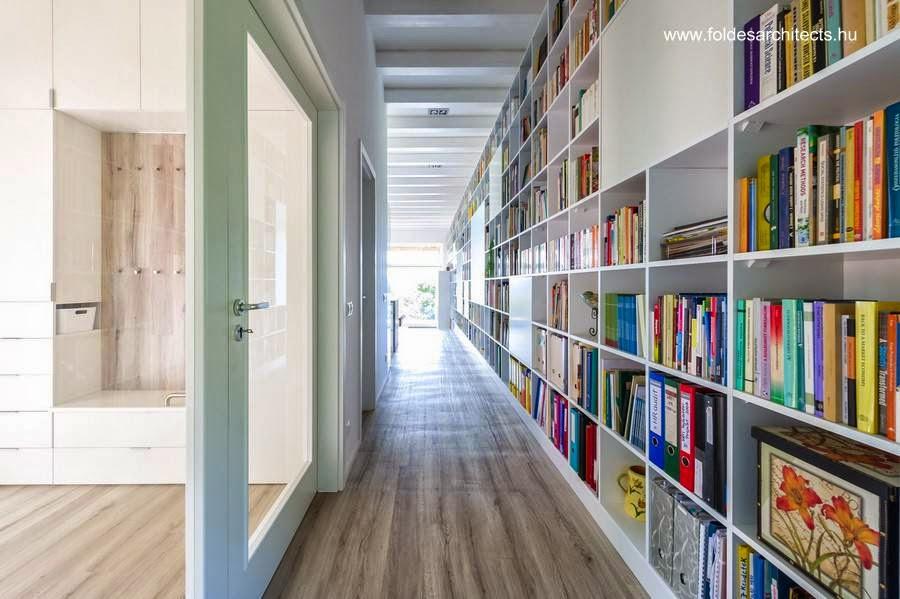 Pasillo y larga biblioteca sobre el muro de la derecha adentro de la casa