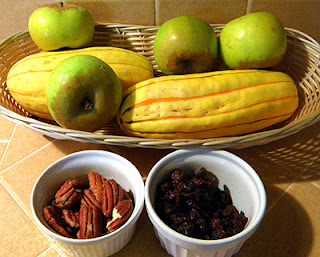 Basket of Delicata squash and apples, dishes of raisins and pecans