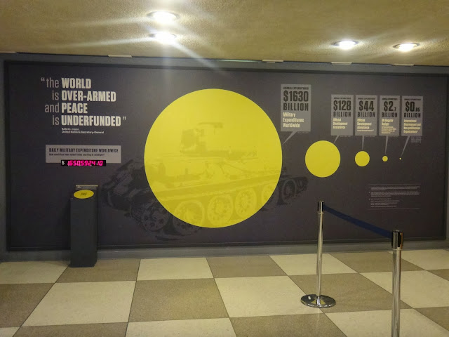 Look at the ratio of worldwide spending where majority goes for military than  focus on country's development, health and education on the exhibition board of United Nations Headquarter in New York, USA