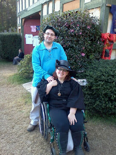 Author seated in wheelchair wearing black leather boots, black leggings, black pirate shirt, & black leather hat, with partner wearing khaki pants, turquoise pirate shirt, and green tam.