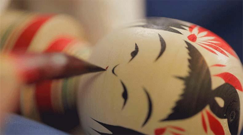 Ve como una muñeca Kokeshi japonés emergen de un bloque de madera que se hace girar