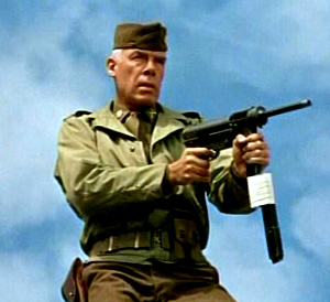 Lee Marvin holding a machine gun in The Dirty Dozen movieloversreviews.filminspector.com