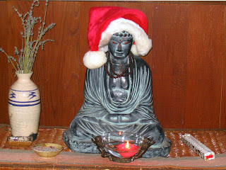 sitting Buddha statue wearing a red and white Santa hat