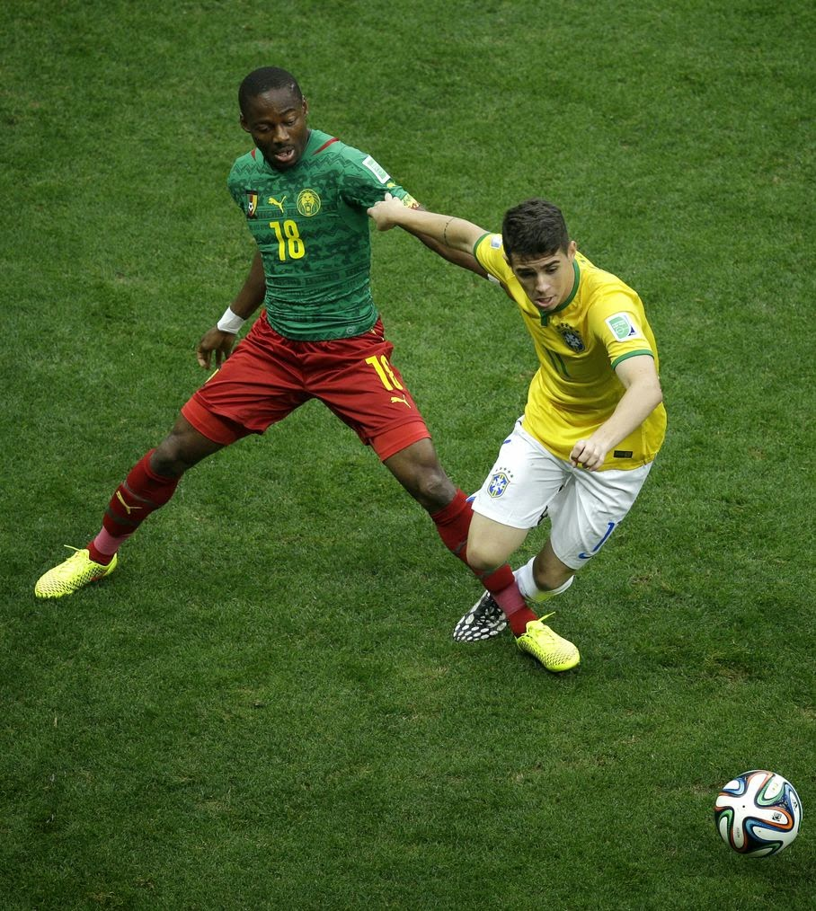 Brazil's Oscar is tacked by Cameroon's Eyong Enoh during the group A World Cup soccer match between Cameroon and Brazil at the Estadio Nacional in Brasilia, Brazil, Monday, June 23, 2014.