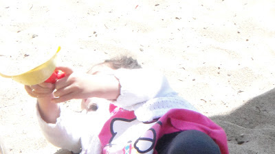 child laying in the sand