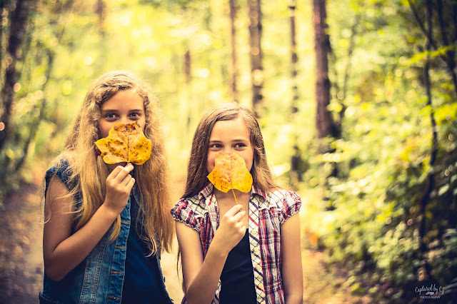 portrait two sisters holding yellow fall leaves in the woods