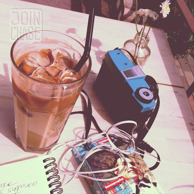 A camera, pen and paper, and an iced latte in Hongdae, Seoul, South Korea.