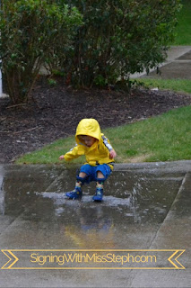 Boy wearing a rain coat and rain boots lands in puddle with a big splah