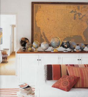 Aparador com globos e um mapa antigo na parede