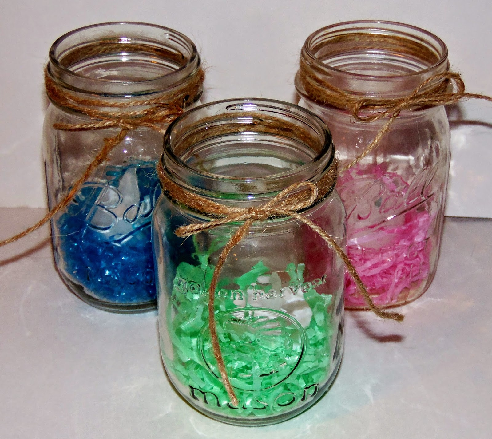 Here Are Three Small Mason Jars With A Bit Of Colored Easter Grass At The Bottom On Top In Each Jar Is An LED Tea Light