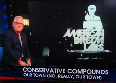 Glenn Beck sitting at left of screen with graphic on a screen in background reading AMERICAN DREAM LANDS with a male figure in a suit over the words