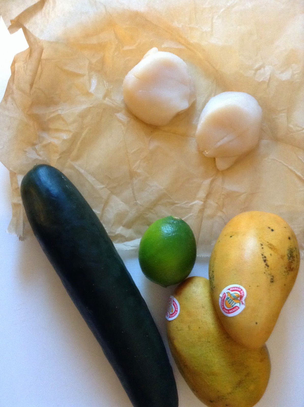 Raw scallops on wax paper with a whole cucumber, two mangos and a lime