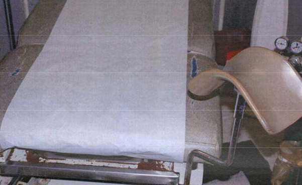 Lower end of a beige gynecological table, showing tears in the cover and caked blood on a metal lip extending beyond the end of the table