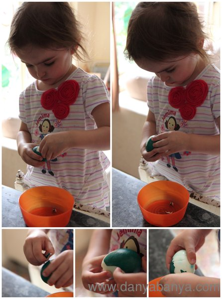 Toddler girl peeling coloured hard boiled Easter eggs