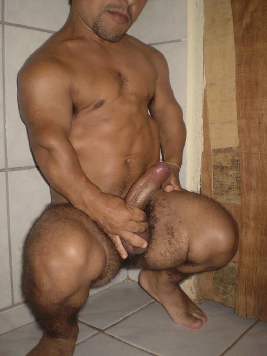 Foto pornô de um anão agachado segurando a pica dura
