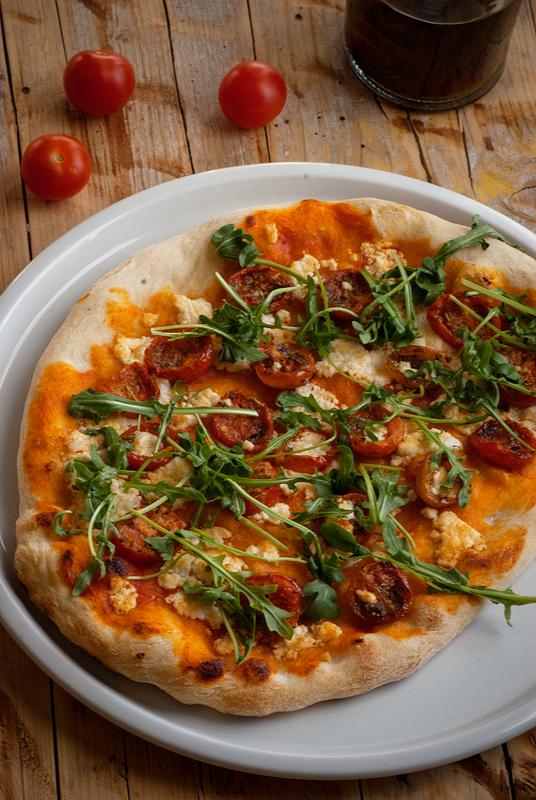 pizza con tomates cheery, queso de cabra y rúcula