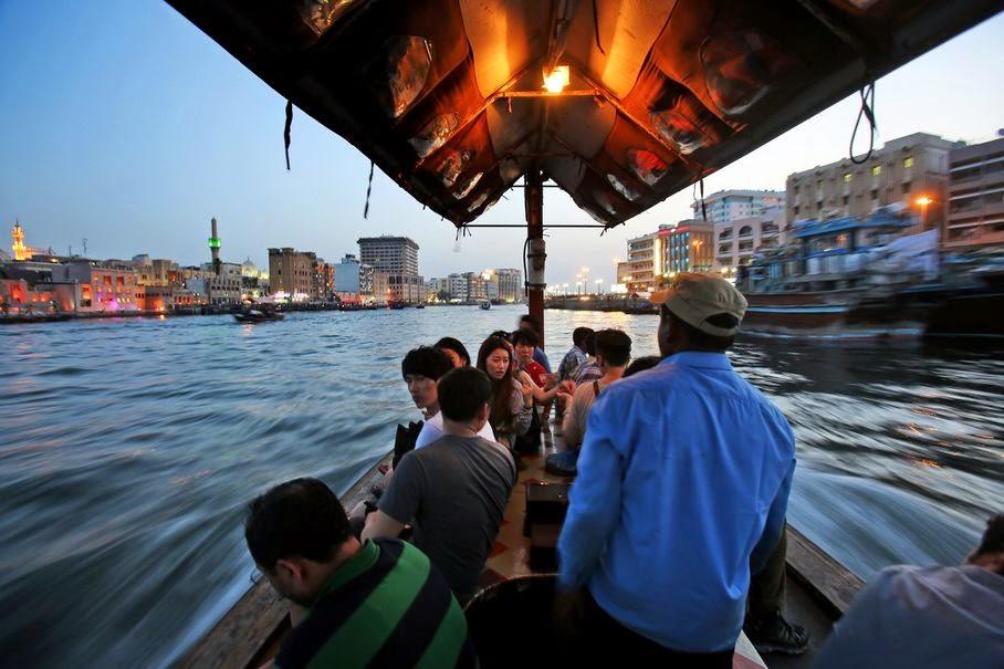 In this Monday, May 26, 2014 photo, tourists and residents cross the creek waters which cuts through the heart of the city, on a traditional abra, or taxi boat, in Dubai, United Arab Emirates. The 14 kilometer (9 mile) Khor Dubai in Arabic or Dubai Creek, is a natural seawater inlet of the Persian Gulf located in the heart of city that runs South to East and ends at Ras Al-Khor wildlife Sanctuary. The creek that divides the city into two parts, Bur Dubai and Deira, has played a major historical role in the economic development of the region.