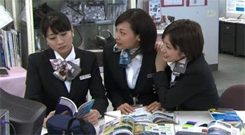 Sekiyama looks despondent while Wakamura and Misaki try to get her interested in the brochures they're looking at.