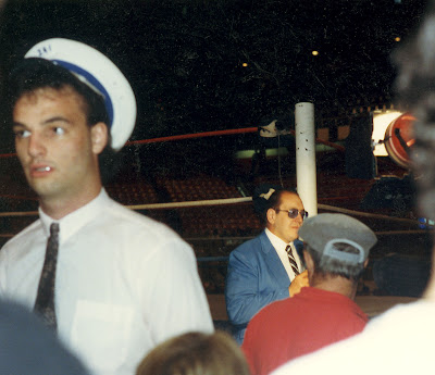 Some guy's external occipital protuberance is blocking the view of Gorilla Monsoon recording another stand-up intro-extro for CHCH-TV's WWF Wrestling at Maple Leaf Gardens. This is from around 1987 or 88, as the Tunneys have had the old NWA ring painted with red, white and blue posts.