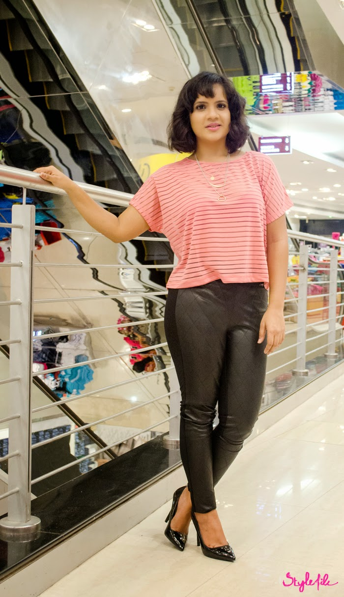 Dayle Pereira of Style File India style a peach sheer striped crop top with pleather paneled leggings from Reliance Trends along with a layered necklace, black pumps and a curly bob
