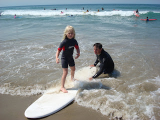 Aloha Beach Camp surf camp instructor Scott Kelly teaches a young child how to surf at summer camp.