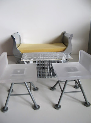 Two modern dolls' house miniature white and grey bar stools from the Kaleidoscope House, a SLICE Tilt coffee table. and a silver sleigh bed.