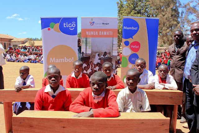 Tigo and HMT donate desks - kids testing them out