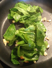 Spinach and garlic cooking on medium heat, starting the filling for Greek Chicken