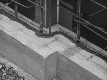 A bentonite waterstop is adhered to a concrete footing prior to casting of the concrete wall above. Later, if groundwater seepage occurs, the bentonite will swell to fully seal the joint between the two pours. The waterstop is positioned to the side of the steel reinforcing bars closer to the wall's exterior, also protecting the reinforcing from moisture and corrosion. However, because of bentonite's expansive force, the waterstop must not be positioned too close to the surface of the wall, or when it swells, it could cause portions of concrete to split away or spall.