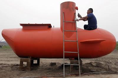 SEORANG pekerja mengecat kapal selam mini yang dibina Wuyi.