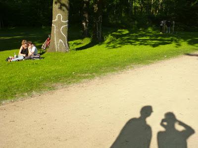 Das Liebespärchen sitzt weiter auf der Wiese, wir sehen aber auch noch als Schattenrisse auf dem Weg einen Mann und eine fotografierende Frau.