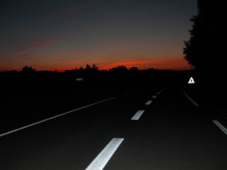 broken white center line of highway illuminated by headlights at night