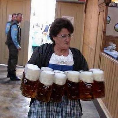 Mulher carregando doze canecas enormes de cerveja.