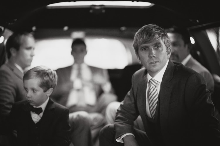 groom sitting with ring bearer in limousine