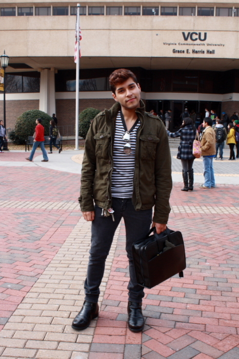 Virginia Commonwealth University student wears a brown bomber jacket over a black and white striped tee blue slim tapered jeans and black boots.