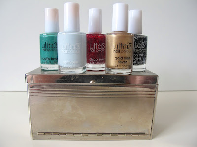 Five full-sized bottles of nail varnish displayed on a metal storage box that looks like a miniature sideboard.