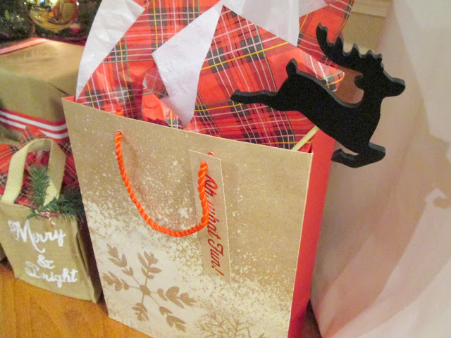 Wrapped Christmas gifts with tree sprigs, striped ribbon, berries, twine, plaid tissue paper and brown paper