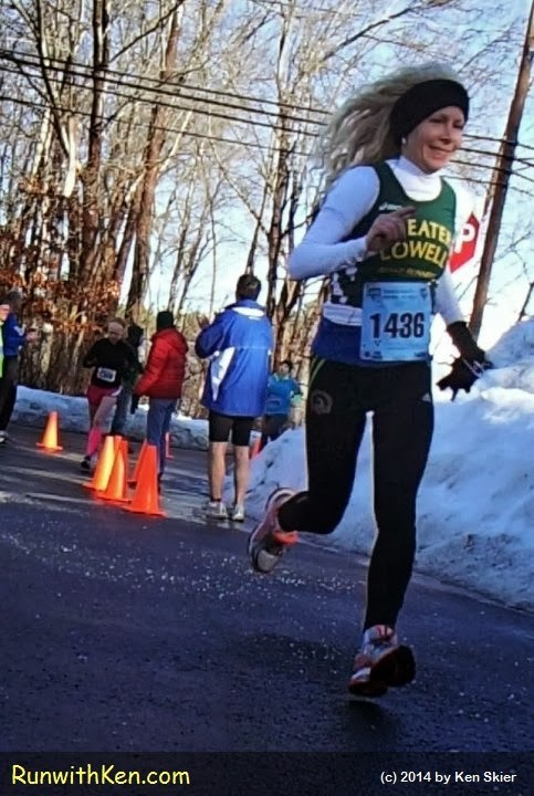 Woman running gacefully--floating just above the street--at a 5K race in winter, in New England