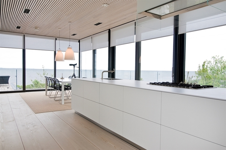 White minimalist kitchen in Modern beach house in Sweden