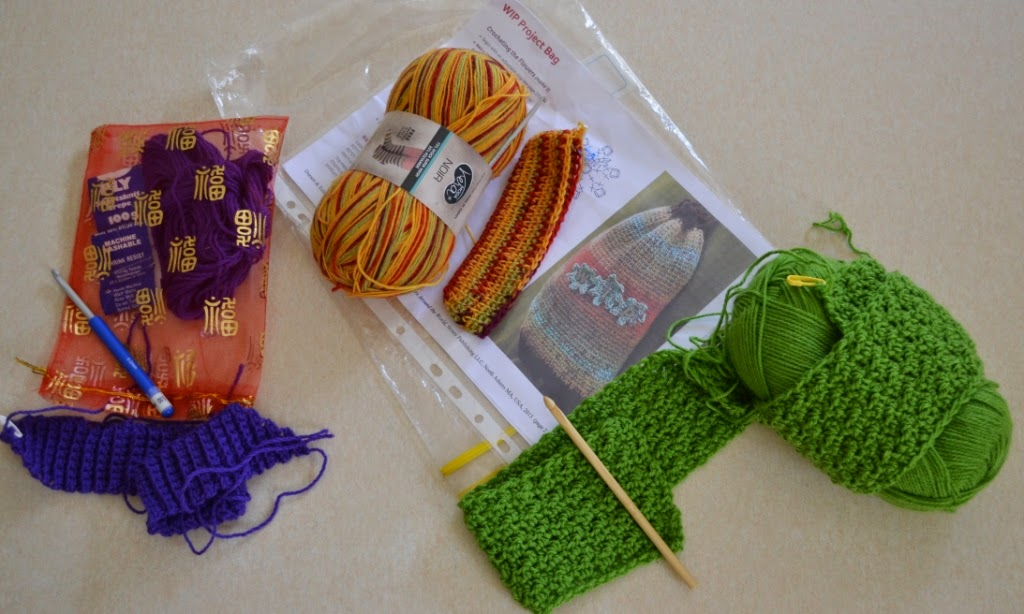 Three new crochet project beginnings. From left to right: Purple tie/belt for Belcarra Cardigan, WIP project bag in stripey yellow, red and green sock yarn, lime green baby blanket in DK acrylic.