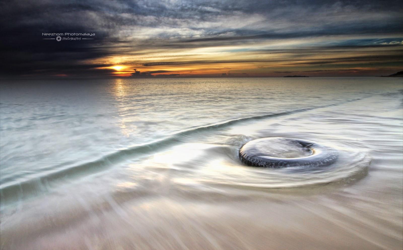 Sunrise dan tayar di pantai Batu Buruk