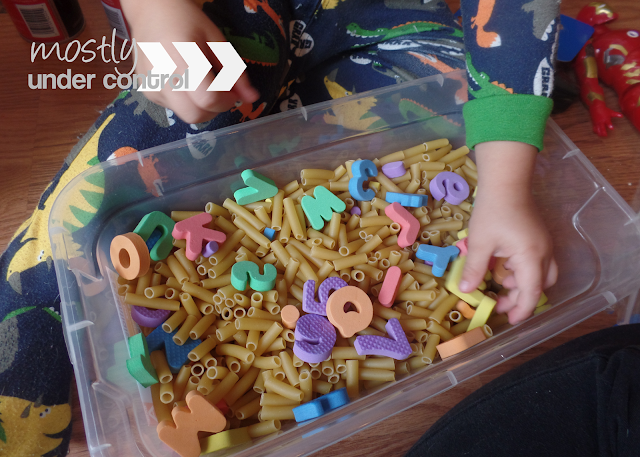 sensory bin with dry pasta and letters