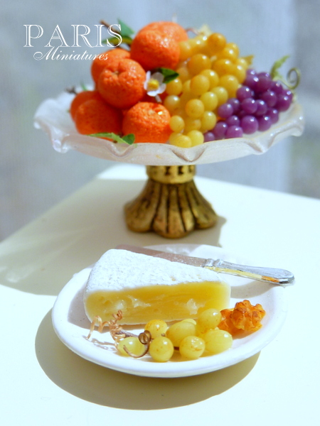 Miniature plate containing brie cheese with grapes and walnuts with a fruit display in the background