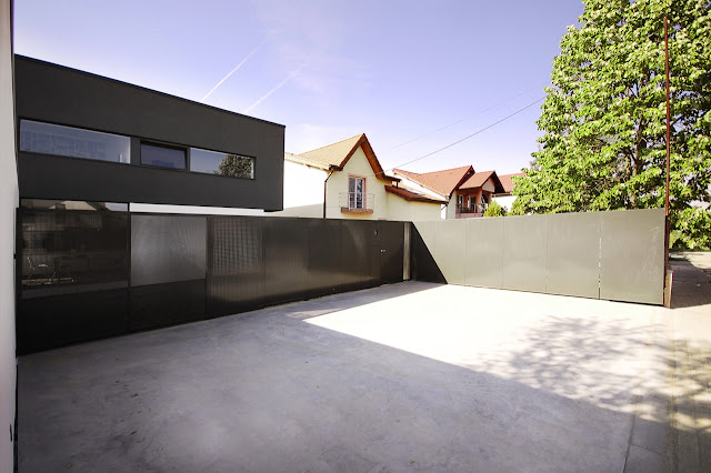 Driveway and modern fence of Black On White House by Parasite Studio