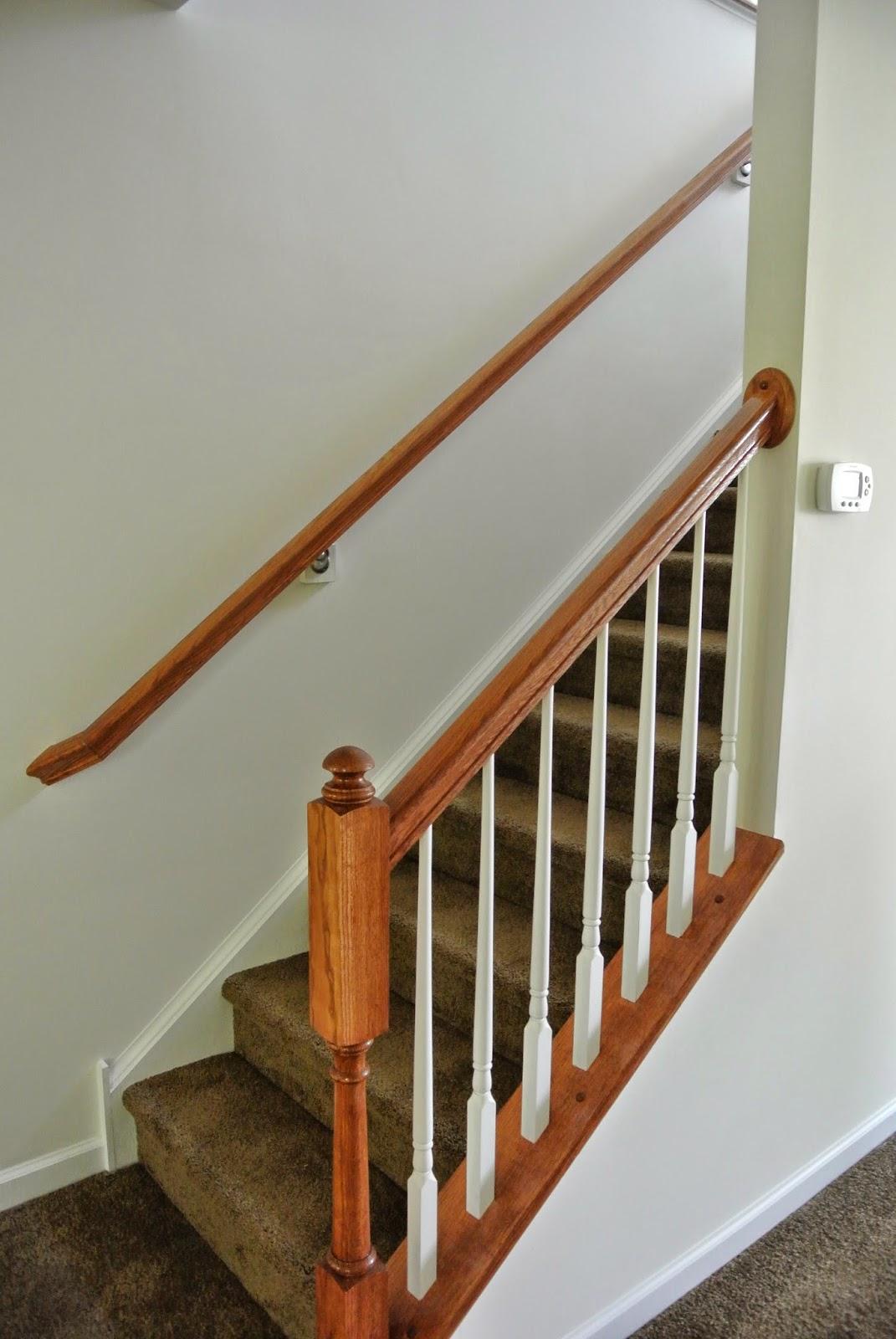 A picture of the finished banister and railing at the bottom of the stairway to the second floor.